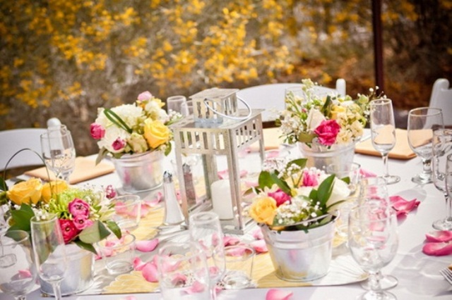 add color to your table setting with bright floral centerpieces in buckets for a rustic feel