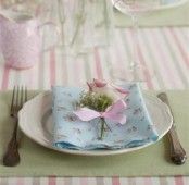 a simple pastel place setting with a floral napkin, a green placemat and a flower