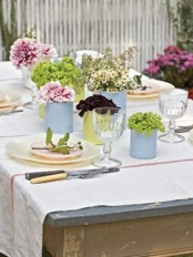a pastel spring tablescape with pastel tin cans instead of vases and spring blooms, pastel plates and chargers
