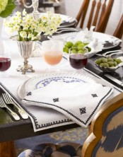 a simple spring palce setting with printed porcelain and napkins, with a fresh bloom centerpiece
