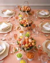 a colorful spring tablescape with a peachy pink tablecloth, bright tulip centrpieces in baskets, and gilded touches