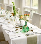 a fresh spring table setting with colorful bloom centerpieces, white napkins, a green runner and white porcelain
