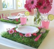 a colorful place setting with a faux grass and bloom placemat and a hot pink bloom centerpiece