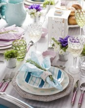 a pastel place setting with printed plates and chargers, pastel glasses, greenery and moss