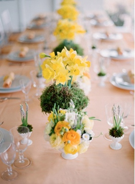 a bright spring centerpiece of yellow blooms, moss and bulbs