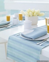 a pastel spring tablescape in powder blue and white, with striped textiles and a neutral floral centerpiece
