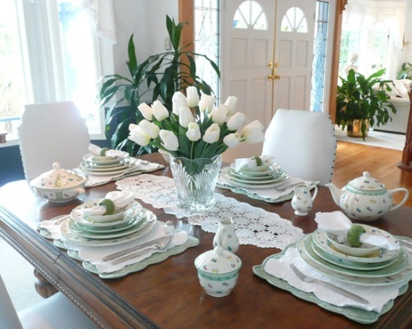 a fresh green and white spring tablescape with lace runners and placemats and a white tulip centerpiece