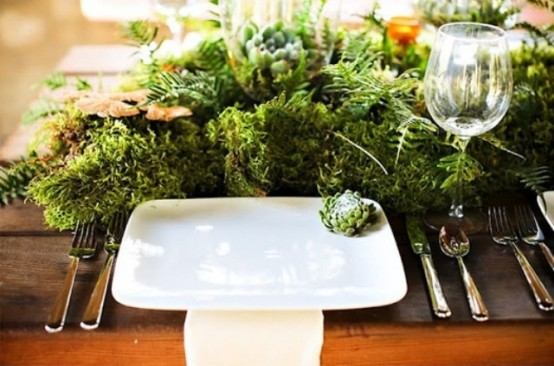 a modern place setting with a lush fern, moss and greenery centerpiece
