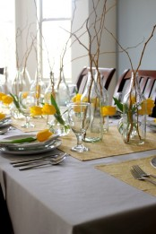 an off-white tablecloth, yellow printed placemats, yellow tulips and branches for centerpieces