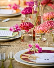 a colorful rustic spring setting with a burlap tablecloth, bright floral centerpieces and plates
