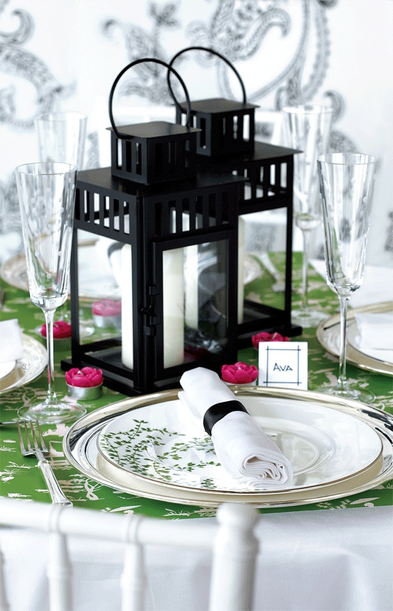 a colorful place setting in green, pink and with candle lanterns