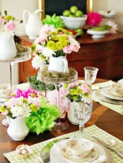 a super bright spring centerpiece with pink, blush, green and yellow blooms and moss