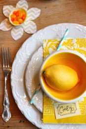 a chic place setting with white plates, a yellow napkin, a yellow bowl and a lemon