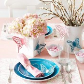 a pink and blue place setting with bright plates, hydrangeas and butterflies