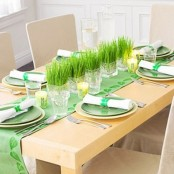 a bright green spring tablescape with a green runner and plates and fresh grass centerpieces