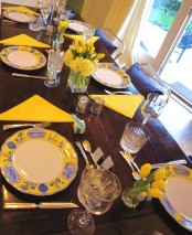 a simply bright spring tablescape with yellow napkins, yellow tulips, patterned plates