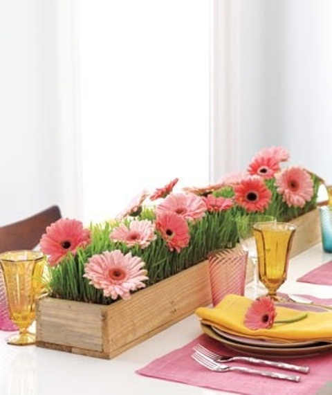 a colorful spring table setting with bright floral centerpieces, colorful napkins and glasses