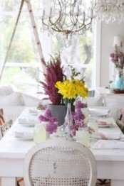 a neutral spring table setting with bright floral centerpieces in purple and yellow