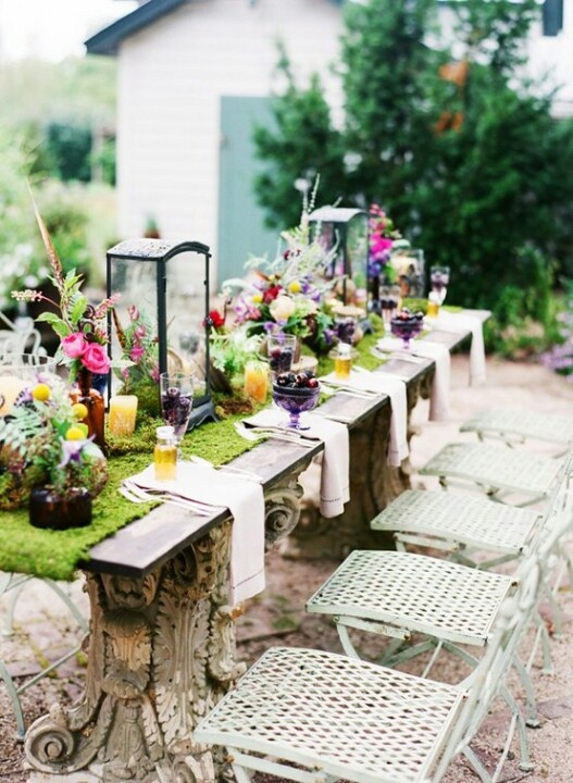 a spring table setting with a moss runner, colorful blooms and lanterns