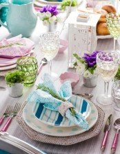 a colorful place setting with striped and polka dot plates and colorful glasses