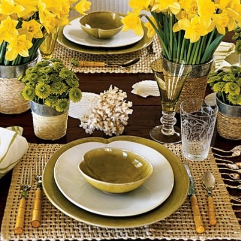 a place setting with a burlap placemat, yellow bloom centerpieces