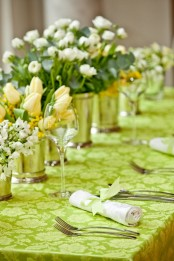 a green printed tablecloth, lush white and yellow flower centerpieces for spring