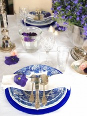 a spring place setting with printed blue plates and purple blooms