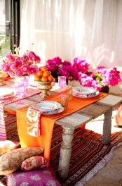 a super bright and colorful table setting in Moroccan style, with pink blooms, colorful napkins and runners and bright pillows
