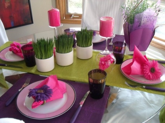 a colorful spring tablescape done in purple, pink and pistachio green plus greenery in pots