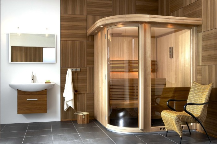 a tiny steam room clad with wood and glass, with a single wooden bench and some built in lights