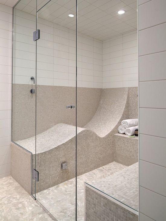 a stylish neutral steam room clad with small mosaic and white subway tiles, with curved benches clad in tiles that are very comfortable