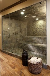 a large steam room clad with grey tiles in various patterns and with a single large bench plus a glass door is very cool