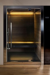a tiny dark steam room with stone walls, a floating bench and built-in lights is very relaxing