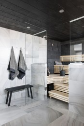 a steam room clad with black tiles and with wooden benches on several levels plus built-in lights