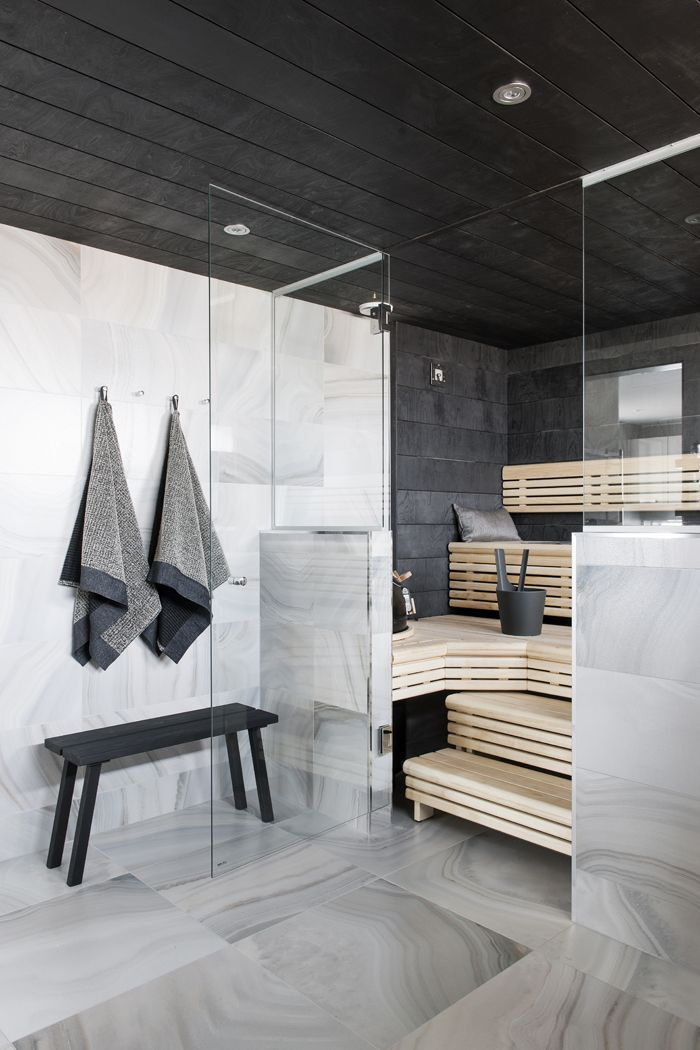 a steam room clad with black tiles and with wooden benches on several levels plus built in lights