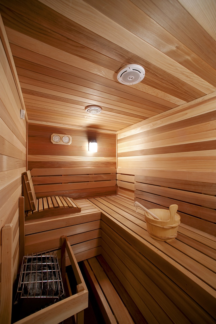 a super cozy steam room clad with wood, with benches at various levels and some built in lights