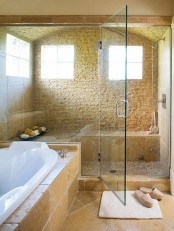 a light-filled steam room clad with stone and matching tiles, with a large bench and some bowls with shower poufs and foams