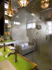 a large steam room clad with grey and green tiles, with windows and a real tile sofa for sitting