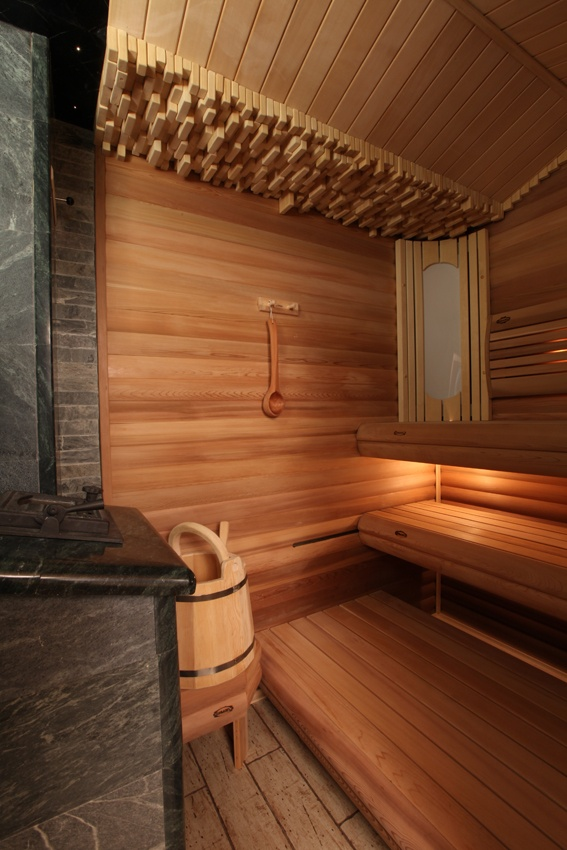a lovely wood clad steam room with benches at various levels, bricks on top and built in lights