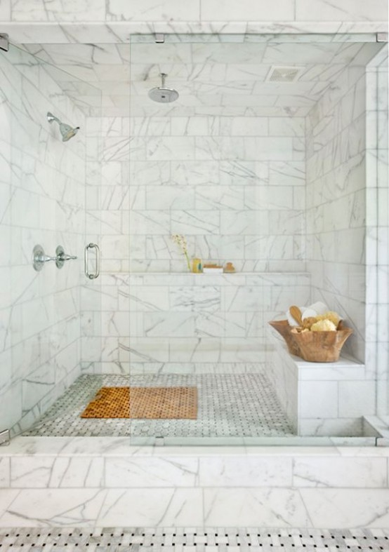 a refined white marble steam room with a tile clad bench and shelf and wooden bowls with foams and scrubs