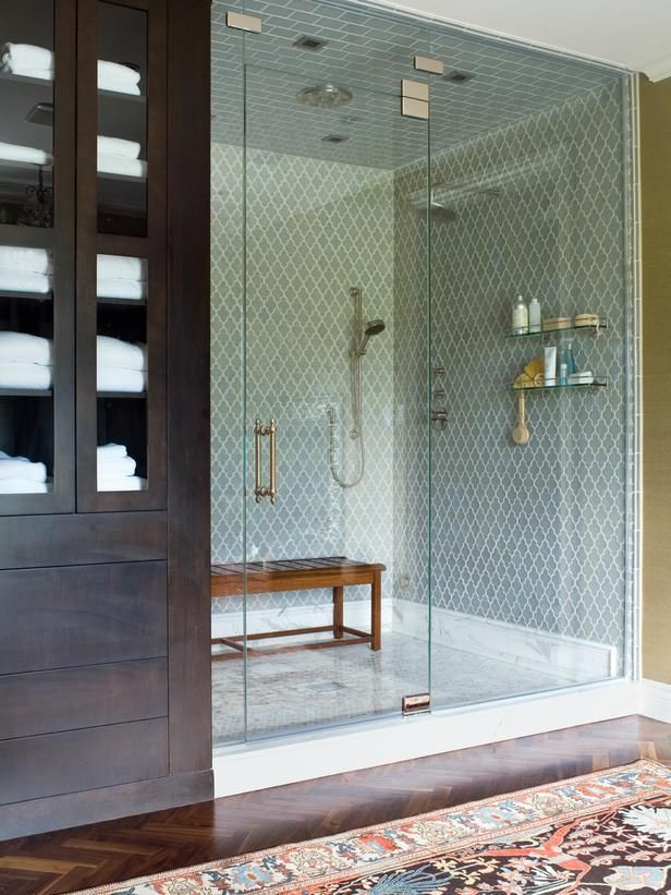 a small yet stylish steam room clad with blue tiles, with a wooden bench and everything necessary