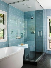 a small steam room with blue and black tiles, with a built-in niche for storage and a bench of wood