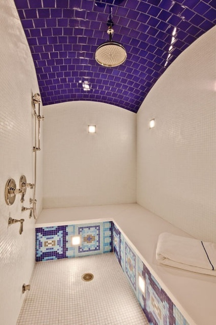 a bold steam room clad with purple and white tiles, with a large tile clad bench and some patterns all over the bench