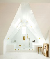 an attic white steam room with a window, two tile clad benches and gold fixtures looks airy and chic