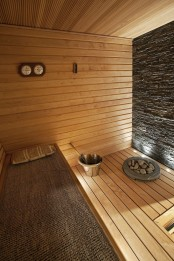 a cozy wood clad steam room with a stone wall and several benches, with a jute cover on one of them and some lights