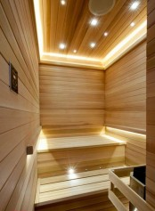 a modern steam room clad with wood, with lots of built-in lights to make the space more welcoming