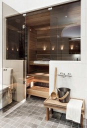 a small steam room clad with wood, with benches at several benches and built-in lights and smoke glass doors