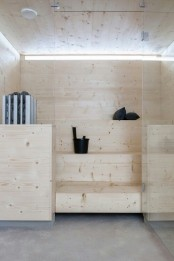 a tiny steam room clad with wood and with step benches plus a narrow skylight for a more natural feel here