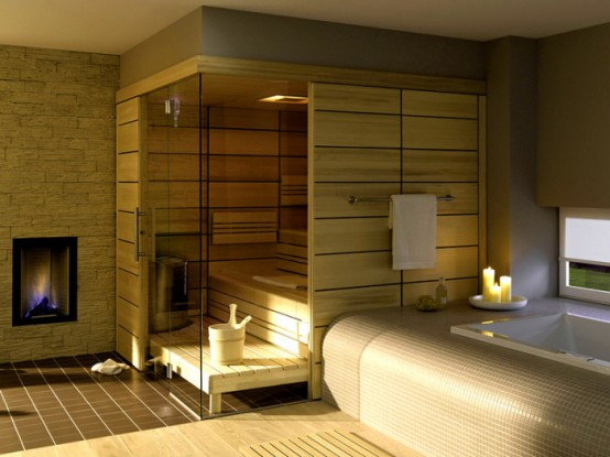 a tiny steam room clad with light-colored wood, with step benches and some built-in lights and a hearth is amazing