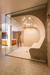 a stylish neutral steam room clad with small scale tiles, with a single bench that appers curved  from the wall